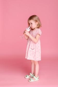 분홍색 표면에 맛있는 우유와 소녀