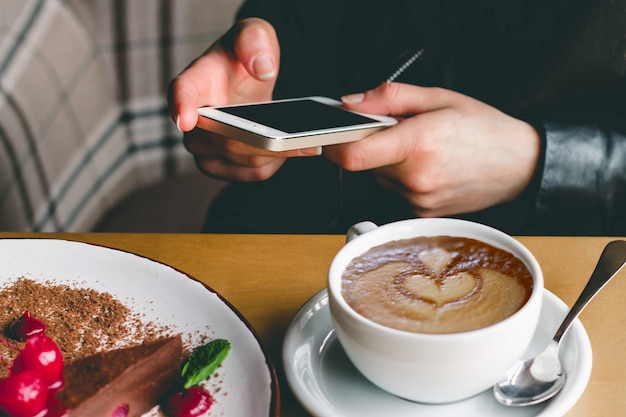 Girl with a mobile phone, coffee and cake in a cafe.