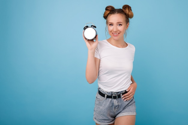 Girl with mock alarm clock on a blue space