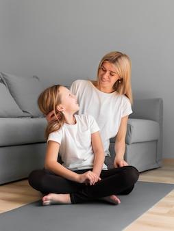 Девушка с мамой спортивной тренировки на коврике