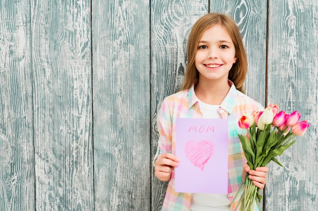 Girl with mother`s day postcard and tulips