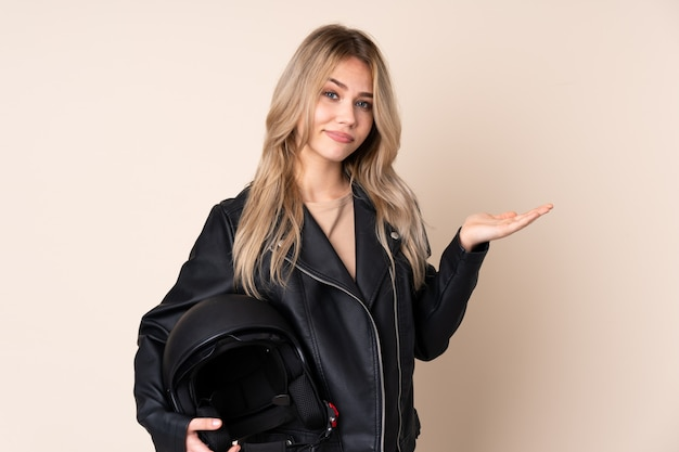 Girl with a motorcycle helmet on beige wall unhappy for not understand something