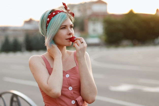 Девочка с разноцветными волосами ест клубнику