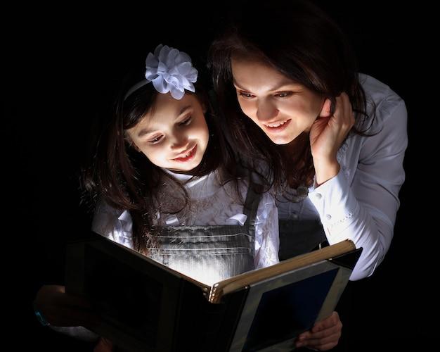 어머니와 함께있는 소녀는 멋진 책을 발견했습니다.