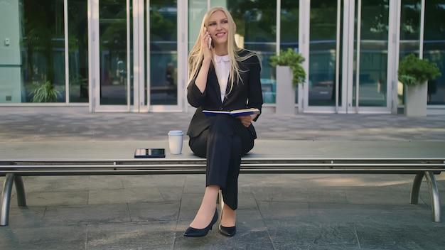 Девушка с блокнотом, говоря на телефоне на открытом воздухе. современная бизнес-леди в костюме сидя на стенде с блокнотом в руках и имея телефонный звонок смотря прочь.