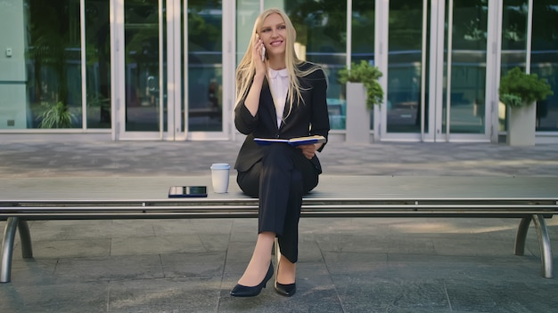 Girl with notepad speaking on phone outdoors. modern business woman in suit sitting on bench with notepad in hands and having phone call looking away.