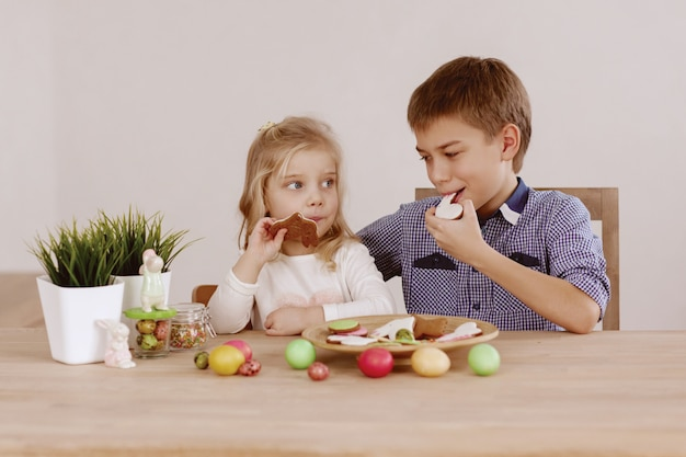 A girl with an older brother are sitting at the holiday table and laying out cookies and easter eggs