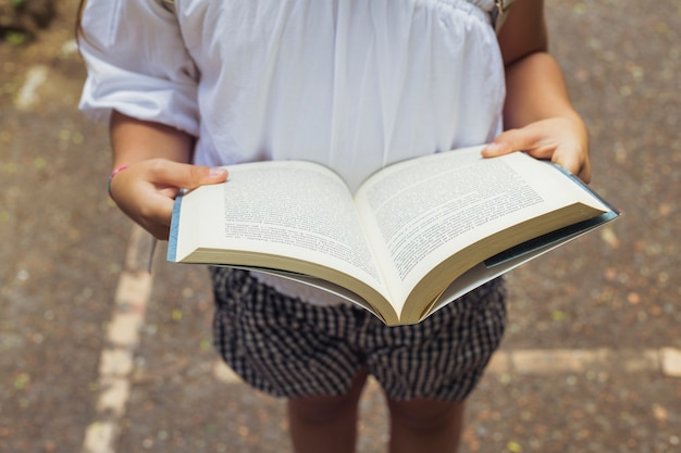 Girl with open book in shorts