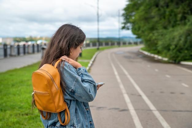 オレンジ色のバックパックを持つ少女が道路に立って電話を見る