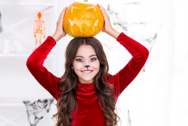 Girl with painted face holding pumpkin on her head