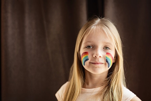 Girl with painted rainbow on face during covid-19 quarantine