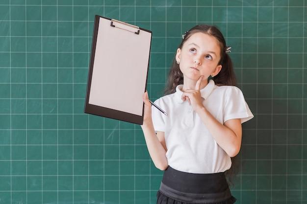 Girl with paper holder near blackboard