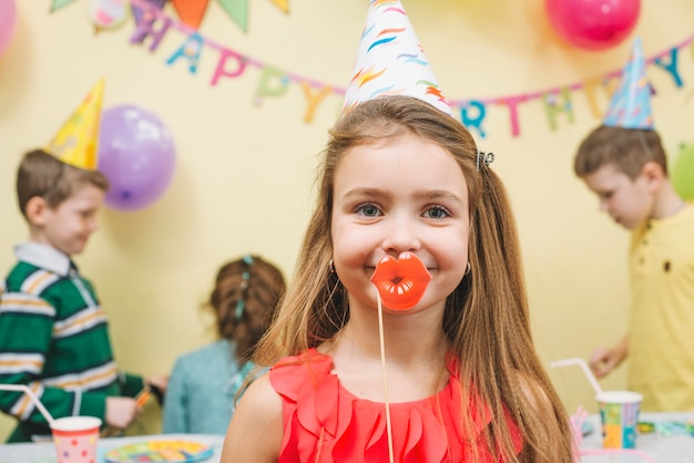 Girl with paper lips on birthday party