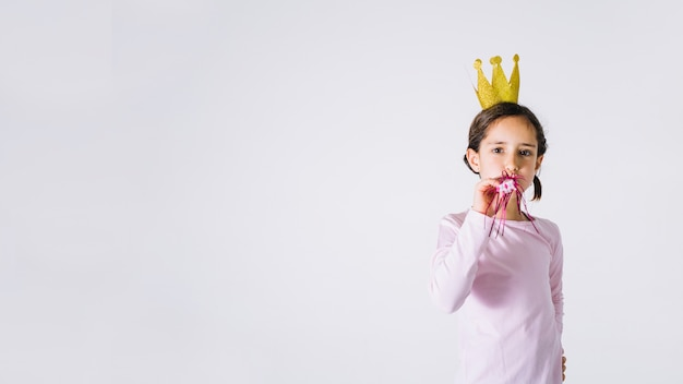 Girl with party horn looking at camera