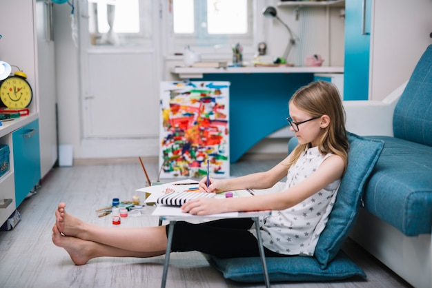 Girl with pencil painting at table in room with water colors on floor