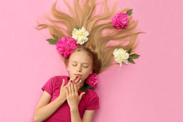 A girl with peonies, beautiful blonde hair and a colorful children's manicure