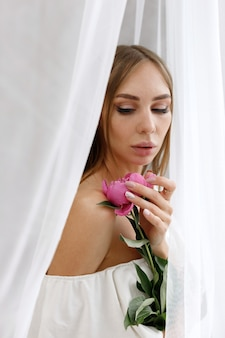 Girl with peony on a white background close-up