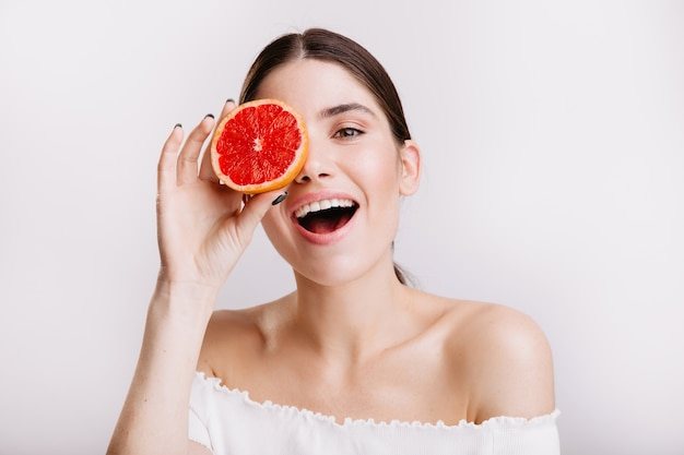 Girl with perfect skin happily poses on isolated wall. portrait of female model supporting healthy diet.