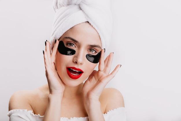 Ragazza con una pelle perfetta pone con macchie sotto gli occhi. ritratto di signora con rossetto rosso dopo la doccia mattutina.