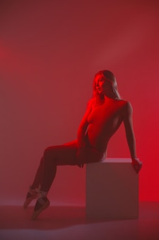 완벽한 슬림 바디를 가진 소녀. 연기에 붉은 빛에 bodysuit에서 포즈를 취하는 여자.