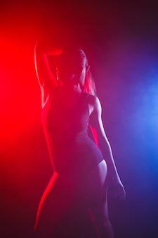 完璧なスリムボディの女の子。煙の中で赤い光の中でボディースーツでポーズをとる女性。