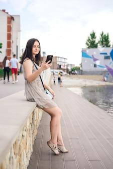Girl with phone on pier.