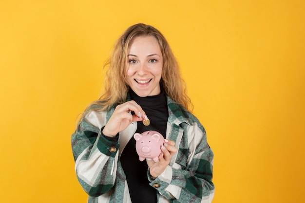 Girl with a piggy bank and a coin in her hands