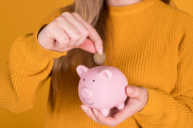Girl with a piggy bank, inserts coins, to save, financial crisis concept