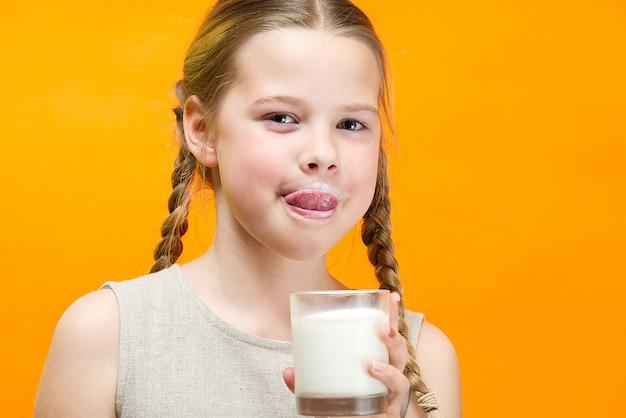 おさげ髪と牛乳の口ひげを持つ少女は、ガラスから牛乳を飲んでいます。 Premium写真