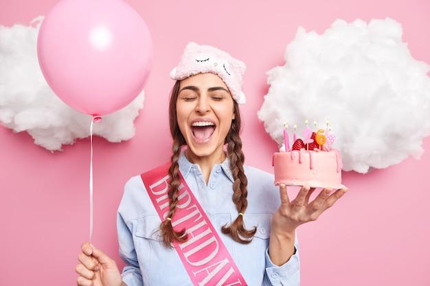 おさげ髪の女の子は大声で睡眠マスクを着て叫び、シャツはピンクに隔離されたおいしいおいしいケーキの膨らませた風船を持っています