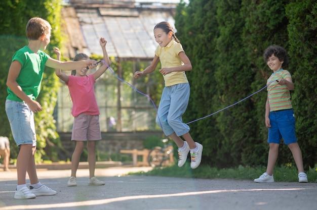 Девушка с косичками прыгает через скакалку с друзьями