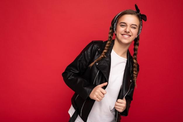トレンディな黒い革のジャケットとモックアップのための白いtシャツを身に着けているおさげの女の子は、カメラを見て赤い背景の壁の上に隔離されています。