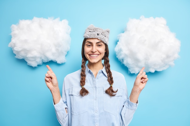 Girl with pigtails wears sleepmask and casual shirt points above on white clouds smiles gently demonstrated product for sleeping isolated on blue