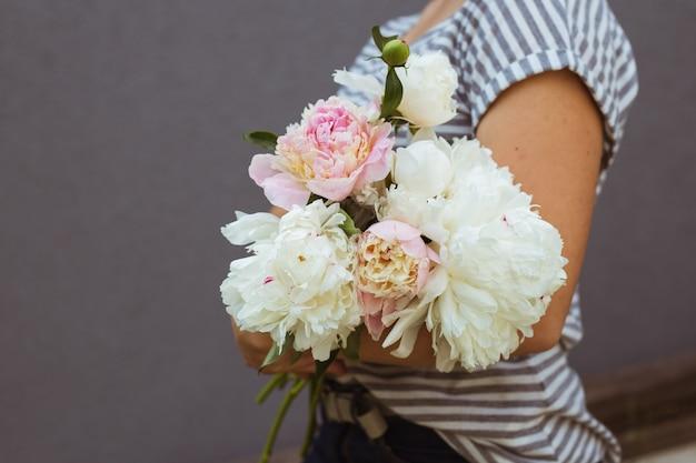 ピンクと白の牡丹の花束を持つ少女