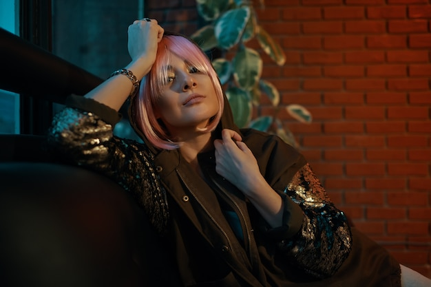 Girl with pink hair sitting relaxed on a leather sofa