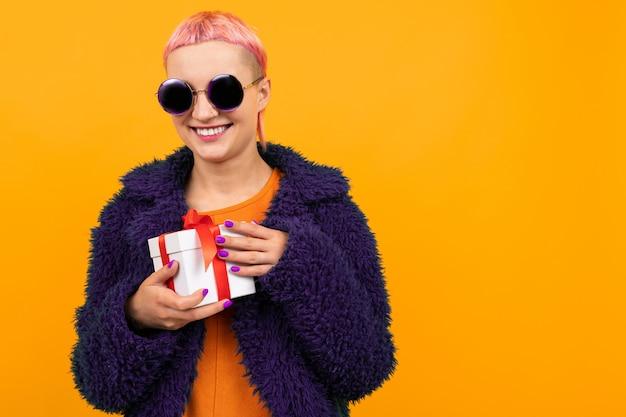 Девушка с розовыми волосами с пирсингом на носу оделась в шубу и очки держит подарок на желтом