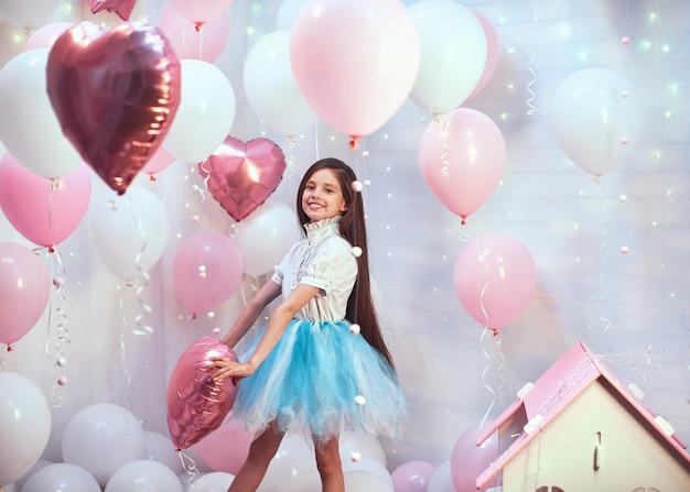 ピンクのヘリウム風船とチュチュを持つ少女