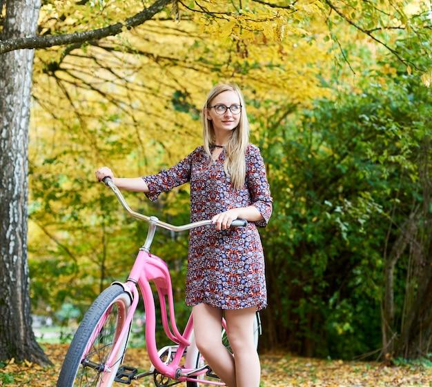 Девушка с велосипедом розовой дамы стоя самостоятельно под высоким деревом на предпосылке красивой зеленой и золотой листвы осени солнечной.