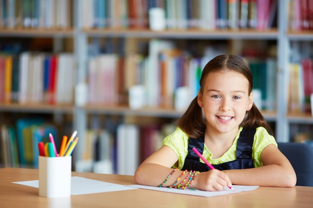 Girl with pink pencil in the library