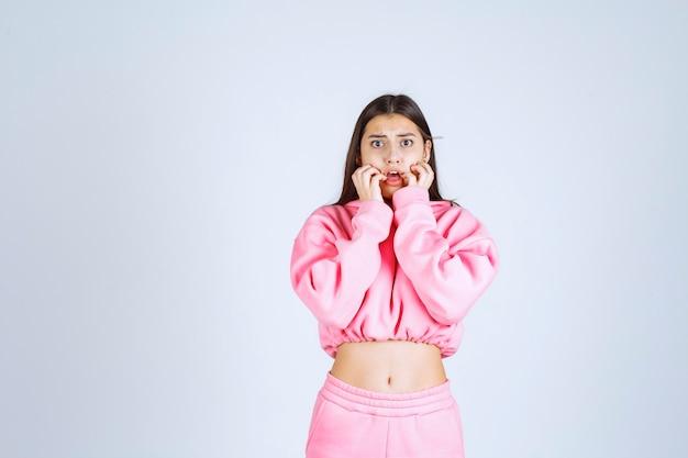 Девушка в розовой пижаме выглядит напуганной и напуганной