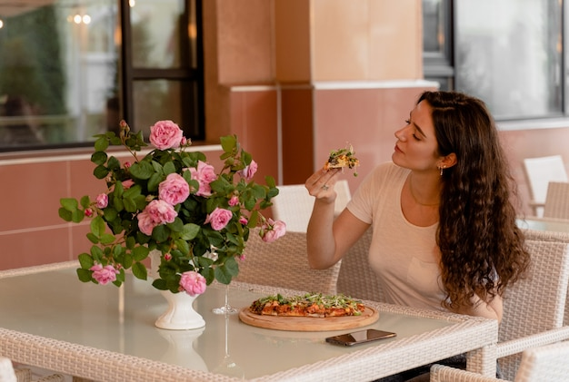 Girl with pinsa romana in cafe on summer terrace. young woman eating pinsa and drinking wine.