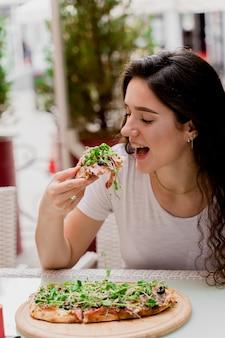 여름 테라스에 있는 카페에서 핀사 로마나를 가진 소녀. Pinsa 먹고 와인을 마시는 젊은 여자. 프리미엄 사진