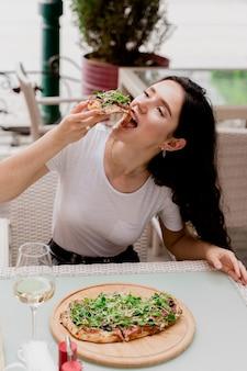 여름 테라스에 있는 카페에서 핀사 로마나를 가진 소녀. pinsa 먹고 와인을 마시는 젊은 여자.