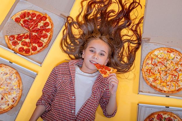 Девушка с пиццей лежит на желтом фоне