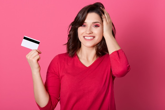Girl with pleasant appearance holding credit card in her hands, wins money in lottery, woman in red outfit looks happy, pays for purchases with card, keeping palm on herd.