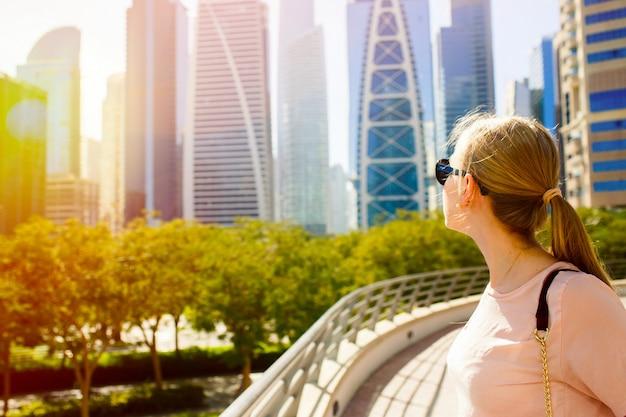 Девушка с хвостиком смотрит через плечо на большие небоскребы