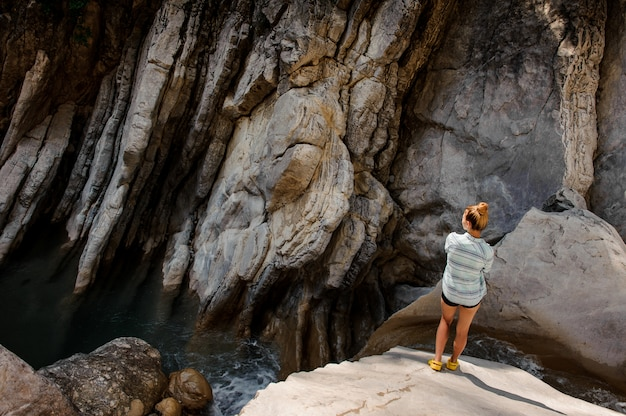 Girl with ponytail standing near waterfall in canyon