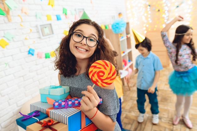 Girl with presents is holding colored lollipop in hand.