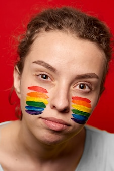 Girl with pride flag painted on her cheeks smiling