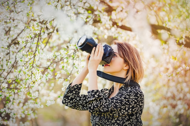 Girl with professional photo camera making images of a flowering tree